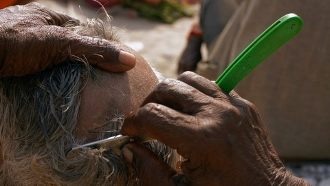Indian barber shaving an old man's white hair head with a blade - Hindu Ritual of donating hair