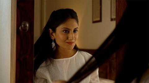 Indian beautiful girl admiring herself in the mirror - good looks, hairstyle