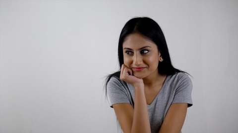 Beautiful Indian girl sitting and smiling - different expressions on the face. White background