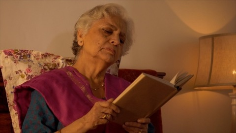 Indian grandmother happily smiling while reading a book at home - old age concept