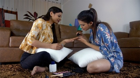 Attractive Indian girl sitting on floor applying nail paint to her friend