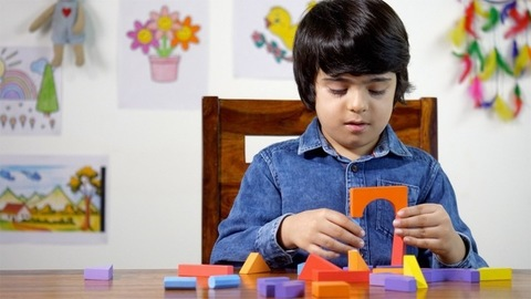 Little Indian boy playing with wooden blocks. Slow-motion shot