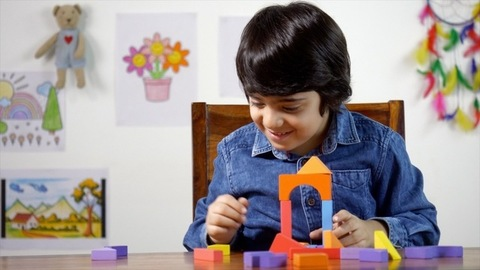 Young Indian boy playing with wooden building blocks and making a house