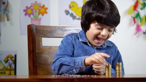 Cute Indian boy happily making a stack of ten-rupee coins - learning the money-saving concept