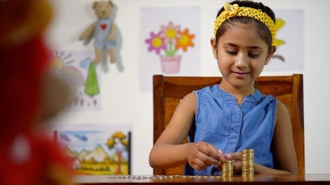 Indian girl making a stack of 10 rupee coins - kids financial concept