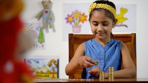 Pretty Indian girl making stacks from coins - kids economy, saving money