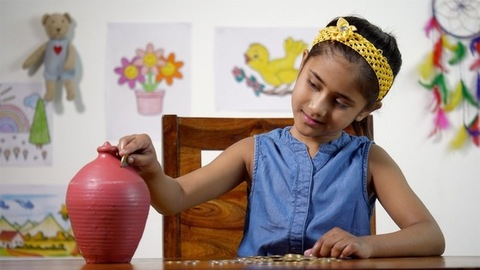 Indian girl inserting coins into a clay money bank (Gulak) - savings concept
