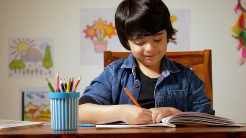 Little Indian boy sitting in his study room and studying - Drawing a picture.Childhood