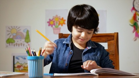Talented Indian boy picking the color pencil to draw a picture - Education in Childhood
