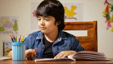 Portrait of a cute Indian boy choosing colored pencil to draw pictures - School homework