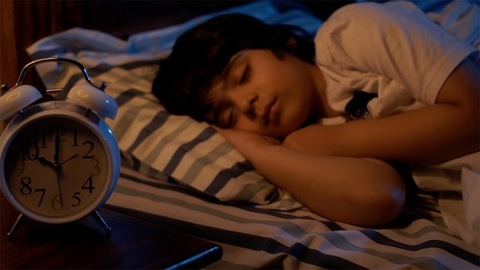 School going cute little Indian boy sleeping in his bed with blanket at night - Tiny dreams