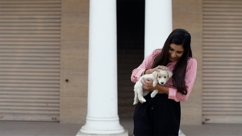 A young beautiful female playing with her white puppy - pet and owner love concept