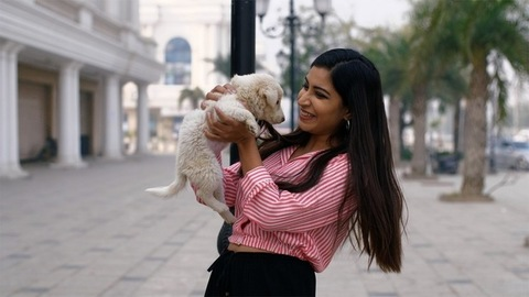 Beautiful young girl having fun with her cute little puppy in the city market in India