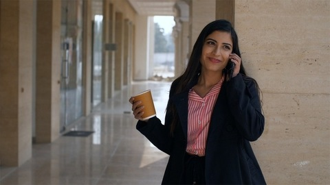 Young office woman having coffee while talking to someone on her smartphone