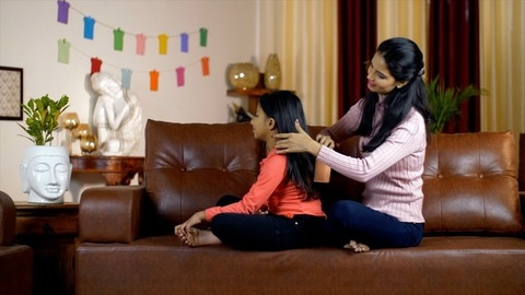 Caring Indian mother combing the hair of her young daughter in the morning - lifestyle concept