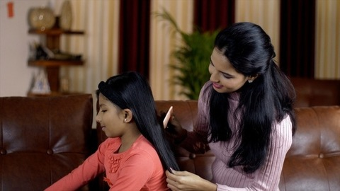 Closeup shot of a loving mom brushing amazing long hair of the cute little daughter