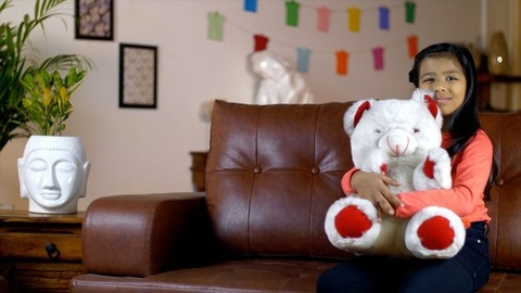 Cute little kid hugging her toy teddy bear at home - happy childhood concept