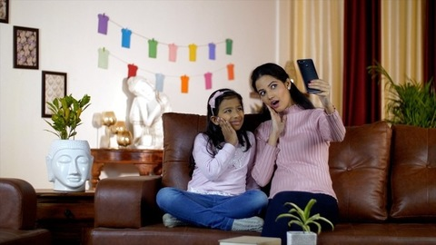 Beautiful young woman taking selfies with her cute daughter at home - winter season