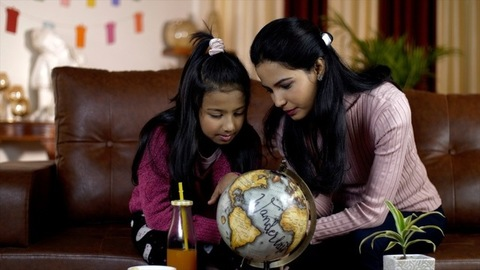 Indian mother and daughter doing school holiday homework with a globe at home