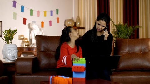 Young businesswoman is annoyed by her naughty daughter while she is busy working