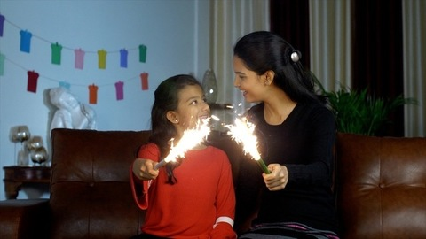 Happy Indian mother and young daughter smiling while holding candle sparklers