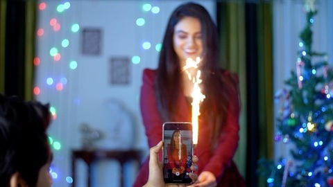 Hands of a young man making a video of her girlfriend holding Anar candle in India