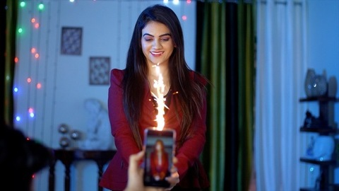 Happy Indian woman smiling and holding candle sparklers in her hand - celebration time