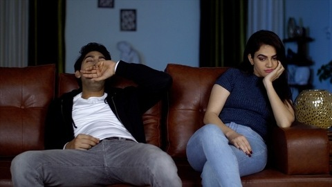 Tired Indian couple sitting in the living room with sleepy bored faces - boredom