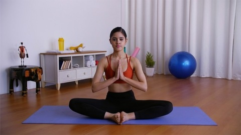 Young sporty girl practicing Parivrtta Upavistha Konasana (revolved seated angle pose)