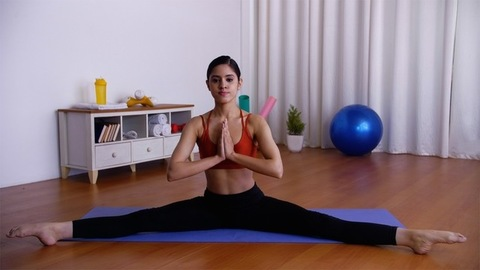Flexible Indian girl doing Parivrtta Upavistha Konasana (revolved seated angle pose)