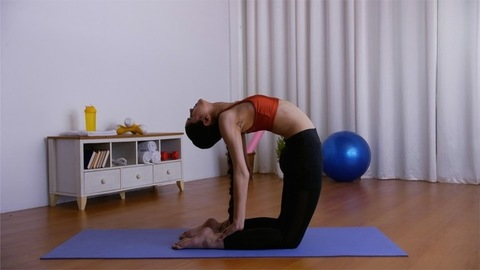 Flexible Indian female performing Ustrasana (camel pose) on a blue yoga mat