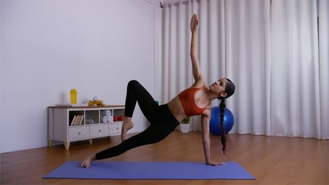 Young flexible girl performing Vasisthasana (side plank pose) on a fitness mat