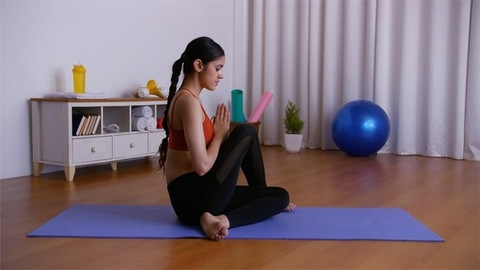 Attractive female athlete doing Ardha Matsyendrasana or Vakrasana on a yoga mat