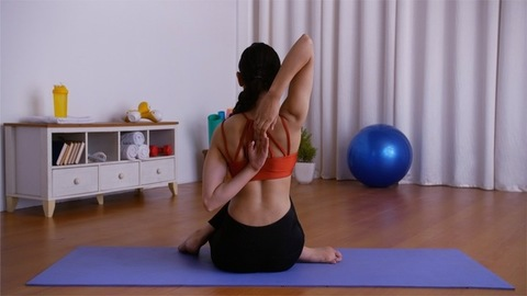 Young sporty girl practicing Gomukhasana (Cow Face Pose) on a blue yoga mat