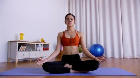 Indian female happily chanting Gayatri Mantra during meditation on a yoga mat