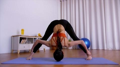 Attractive Indian yogini practicing Prasarita Padottanasana on a blue yoga mat