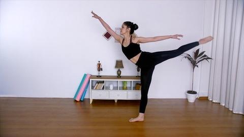 Long shot of a young graceful ballerina practicing ballet in her dance studio