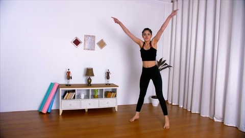 Energetic young trainer demonstrating Zumba dance moves in her fitness studio