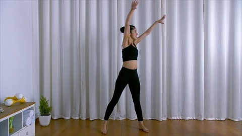 Attractive female athlete happily doing fitness dance moves in casual sportswear