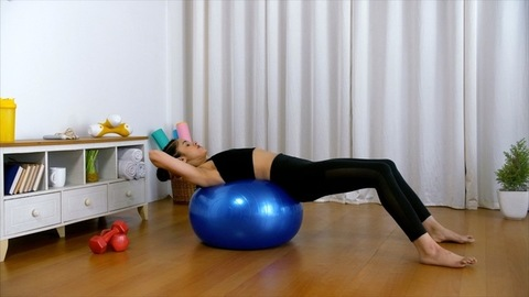 Attractive Indian sportswoman doing a stability workout on a blue exercise ball