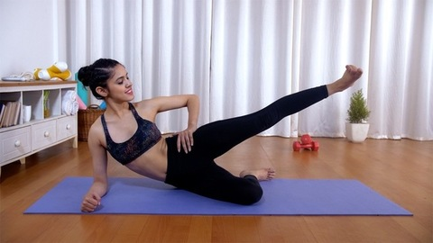 Beautiful Indian girl in sportswear doing side leg lifts while lying on a yoga mat