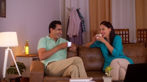 Middle age happy Indian couple sitting on the sofa - laughing, drinking tea, discussion about family matters