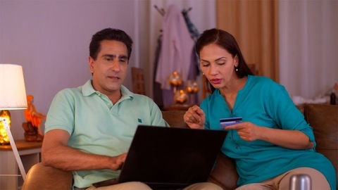 Middle-aged woman and husband doing online shopping using a credit card or debit card - Online payment at an e-commerce website