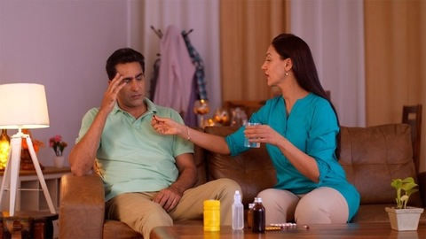 Wife giving a dose to a husband with a severe headache - healthcare and people concept