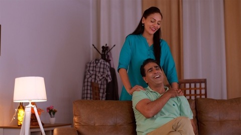 Happy Indian married couple - Wife giving shoulder massage to husband