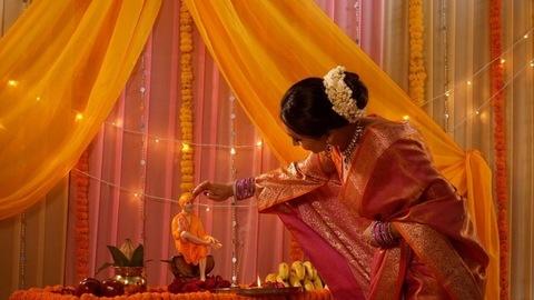 Charming and smiling Indian woman in traditional dress putting tilak on sai baba idol (Sai Pujan)