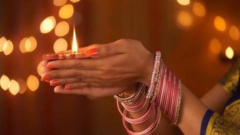 Beautiful hands of an Indian woman wearing bangles - holding a diya. Diwali Festival