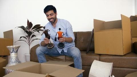 Young Indian man unpacking cartons - moving boxes