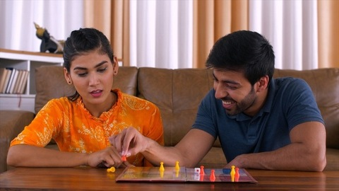 Young Indian Married Couple - Playing ludo board game sitting on floor. Priceless expressions of shock, happiness and jealousy