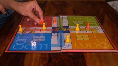 Happy Family - Friends playing ludo board game at table and having a good time